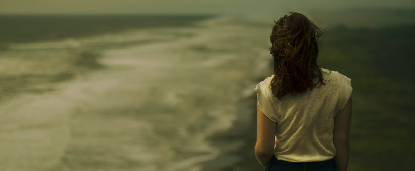 young woman staring out at ocean